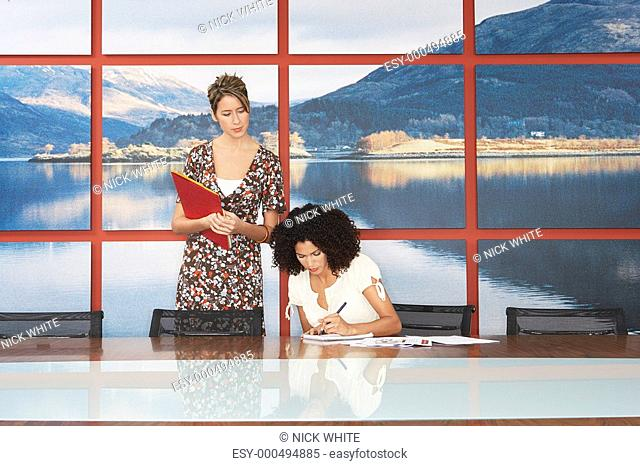 Business woman looking over colleague's shoulder in conference room