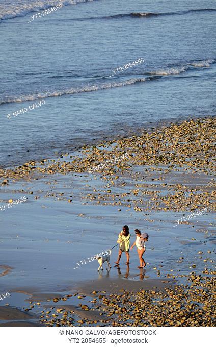 Young girls walking dog on San Antolin beach in Llanes, Asturias