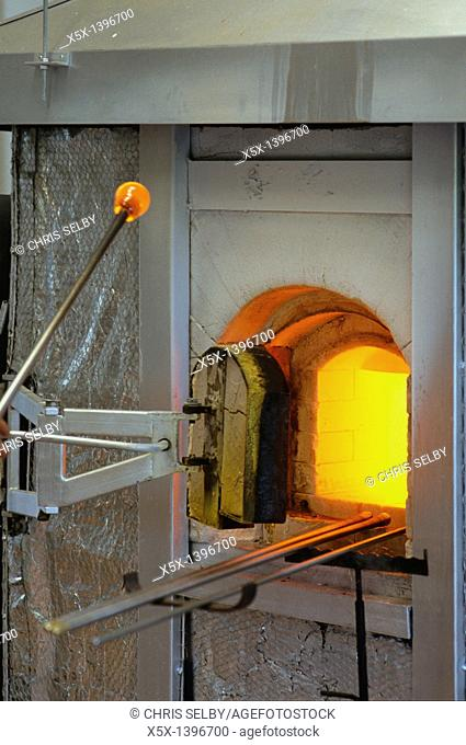 Glassblower removes molten glass from oven