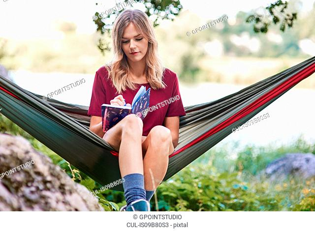 Woman sitting in hammock writing in notebook, Krakow, Malopolskie, Poland, Europe
