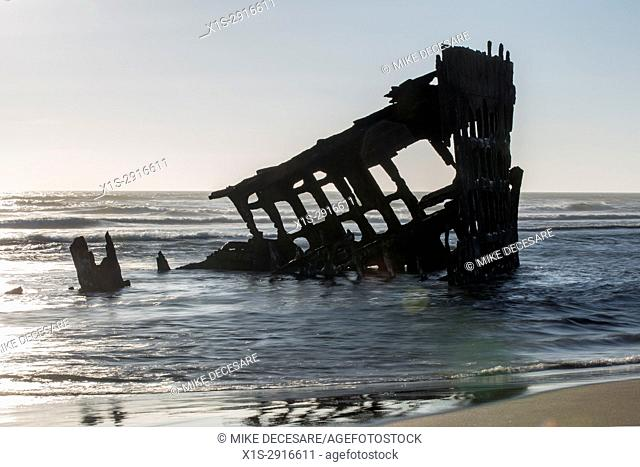Remnants of the steel hull of the Peter Iredale shipwreck can be seen along the shore in Fort Stevens State Park, State of Oregon, USA