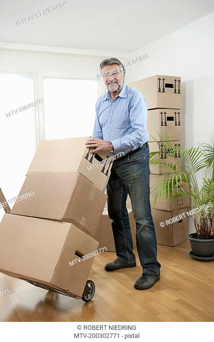 Senior man with moving boxes in new apartment, Bavaria, Germany