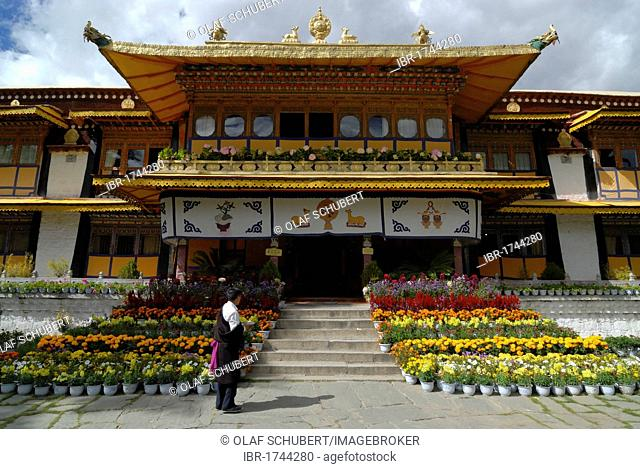Tibetan man wearing a traditional costume standing in front of the summer palace of the Dalai Llama in Norbulingka, The Jewelled Park, with flowers, Lhasa