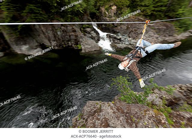 A young man speeds along the West Coast Wild zipline with the Kennedy River flowing underneath him. Tofino,Vancouver Island, British Columbia, Canada