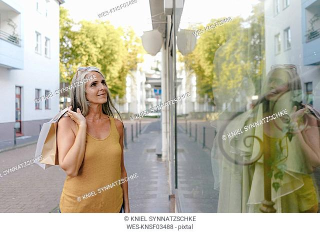 Portrait of smiling woman carrying shopping bags looking in shop window