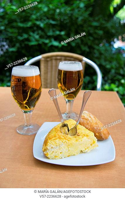 Spanish appetizer: pincho de tortilla and two glasses of beer in a terrace