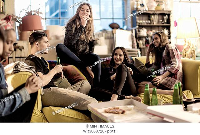 Four young women and young man sitting on a sofa, smiling, pizza and beer bottles on coffee table