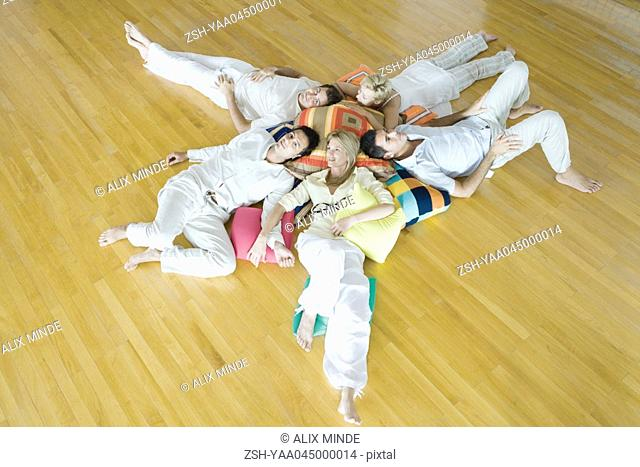 Group therapy, adults lying on ground with heads together on cushions