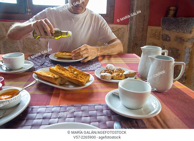 Man pouring olive oil on toasts at breakfast