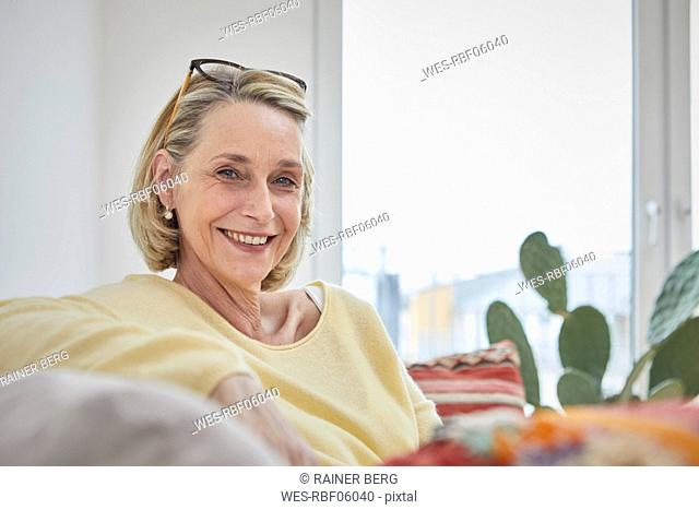Portrait of smiling mature woman at home on the sofa