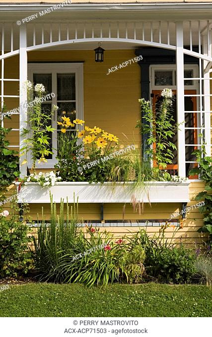Old house veranda with a flower box in summer, Quebec, Canada