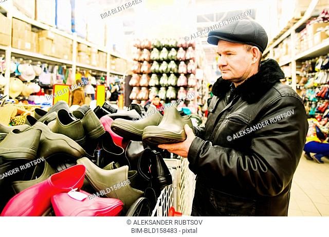 Caucasian man shopping for rain boots in store