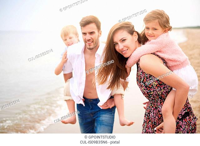 Parents giving children piggybacks on beach