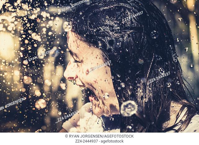 Candid unposed lifestyle image of a beautiful young woman having fun in summer garden with intricate details of drops and water bubbles from a splashing garden...