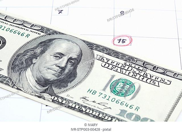 Close-up Of Currency With Calendar
