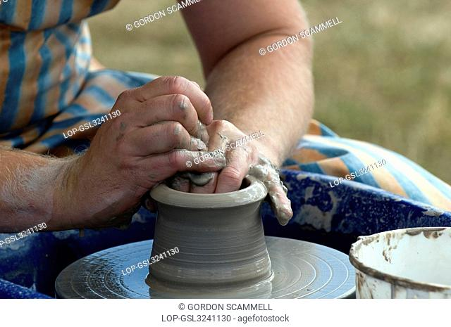 England, Essex, Basildon. Close-up of a potter throwing a clay pot at the Essex County Show