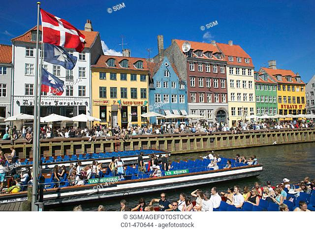 Flags, tour boats, ancient houses and waterfront cafe terraces at Nyhavn ('New Harbor'), Copenhagen. Denmark
