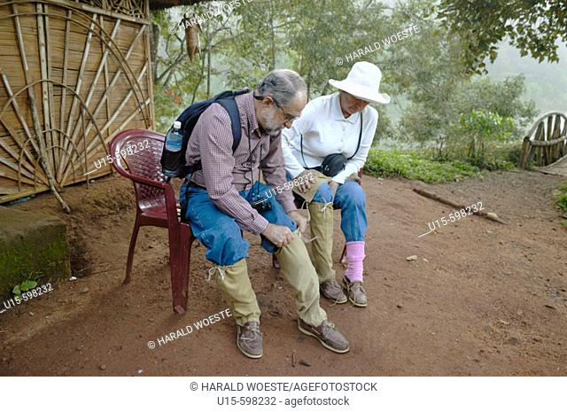 India, Kerala, Periyar Tiger Reserve.  A couple of elderly western tourists in the Periyar Tiger Reserve putting on some leech socks for protection before going...