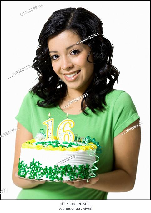Close-up of a teenage girl holding a birthday cake
