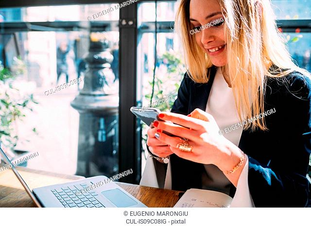 Young woman at sidewalk cafe table looking at smartphone