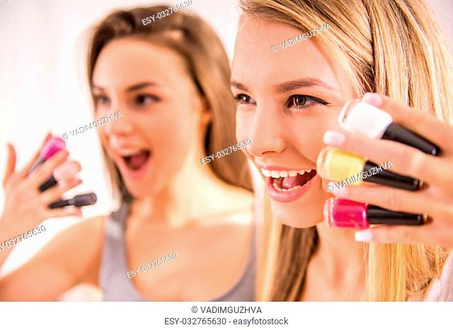 Attractive young women are holding colorful nail varnishes