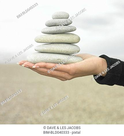 Hispanic woman holding stack of stones