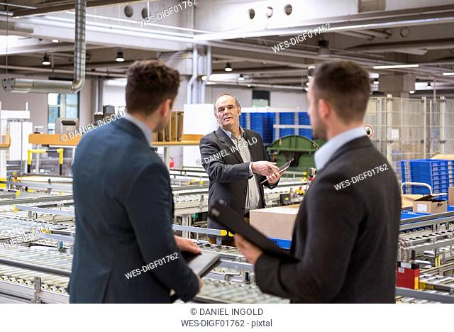 Three businessmen at conveyor belt in factory