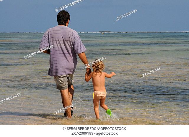 Father with his daughter beach of Amed, a fisherman village in East Bali. Amed is a long coastal strip of fishing villages in East Bali