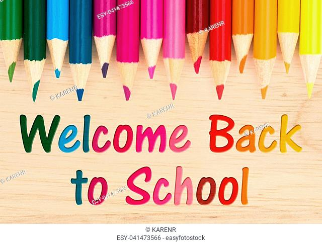Welcome Back to School text with colorful pencil crayons on a wood desk