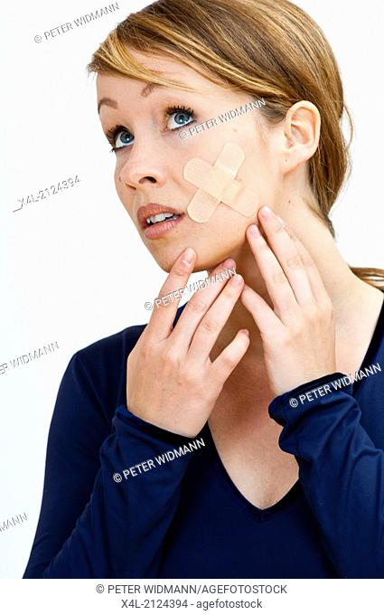woman with an adhesive tape in her face (model-released)