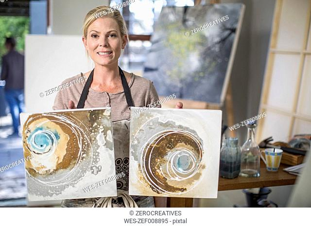 Woman holding artworks in home studio