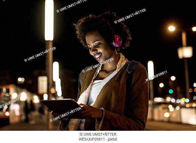 Young woman with tablet and headphones waiting at the tram stop
