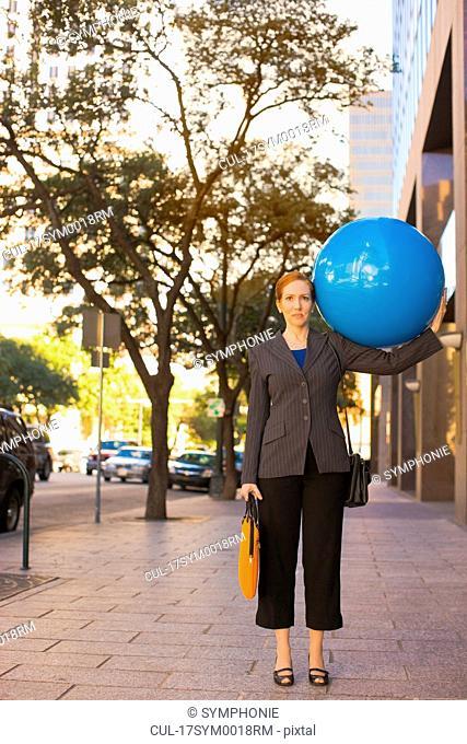 businesswoman holding blue balloon