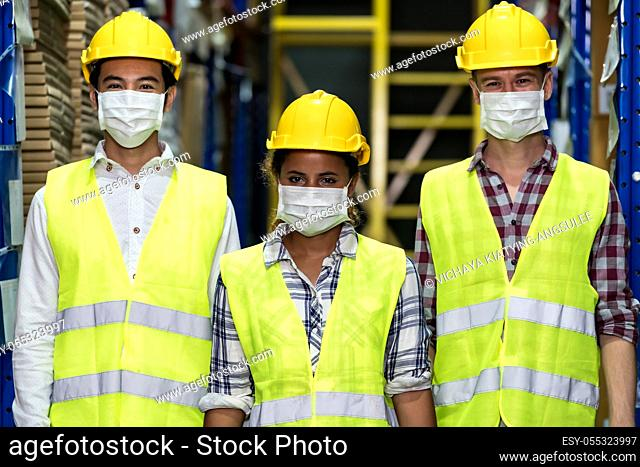 Portrait of Interracial group Asian African and Caucasian warehouse workers team wear face mask to prevent COVID-19 coronavirus infection in distribution center