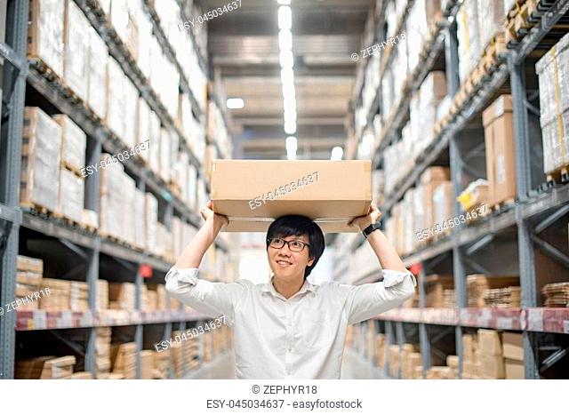 Young Asian man carry paper box over head between row of shelves in warehouse, shopping warehousing or working pick and packing concepts