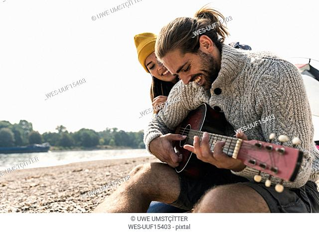 Happy young couple with guitar at the riverside