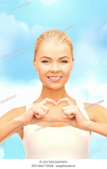 love, happiness and people concept - smiling woman showing heart shape gesture