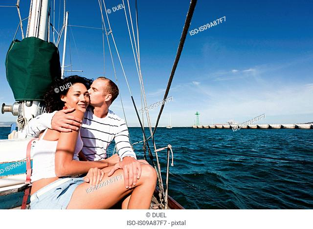 Young couple on yacht, man kissing woman on cheek