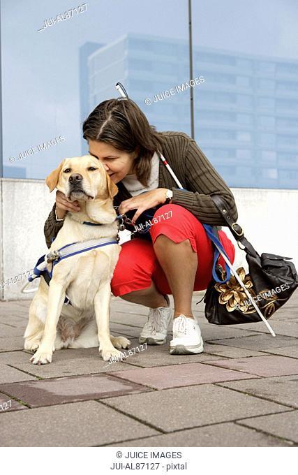 Blind woman hugging seeing eye dog