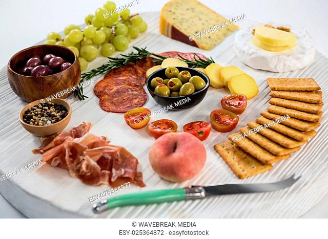 Variety of cheese with grapes, olives, salami, crackers and knife