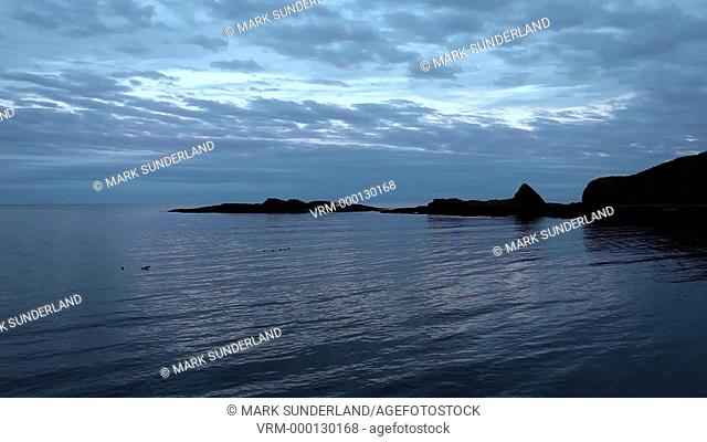 Waves lapping on the shingle in Catterline Bay at dusk on a summer evening Aberdeenshire Scotland