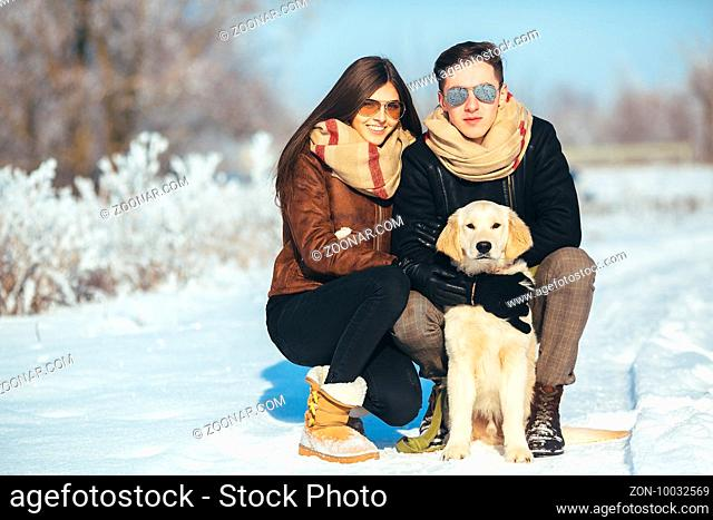 Cute young hipster couple having fun in winter park with their dog on a bright day and smiling