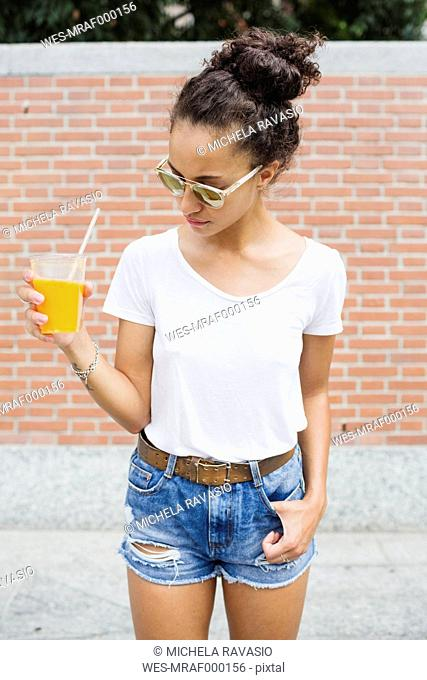 Young woman holding orange juice outdoors