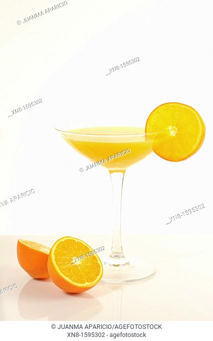 Orange juice cocktail glass garnished with orange slice on the rim of the cup on white background and an orange cut in half at the bottom of the cup
