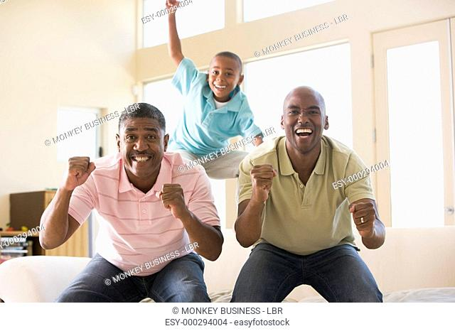 Two men and young boy in living room cheering and smiling