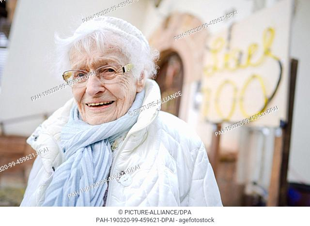 """18 March 2019, Rhineland-Palatinate, Kirchheimbolanden: Lisel Heise stands in front of her house at a sign with the inscription """"""""Lisel 100"""""""""""