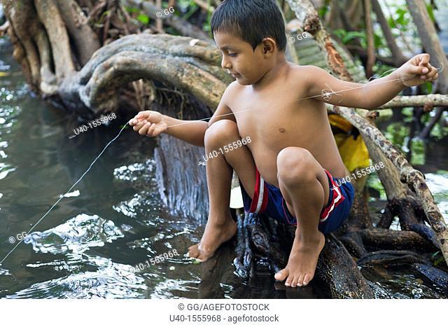 Guatemala, Rio Dulce, boy fishing in river
