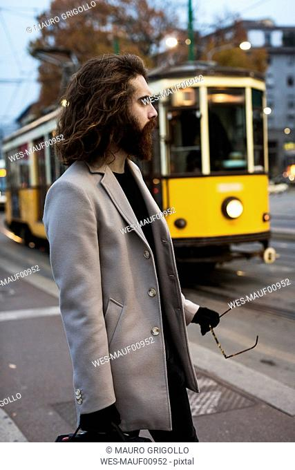 Stylish young man standing at tram stop