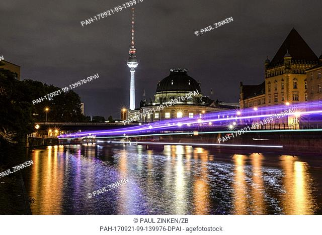 Lights are reflected in the river Spree in front of a skyline dominated by the Bode Museum (C) and the Television Tower at Alexanderplatz in Berlin, Germany