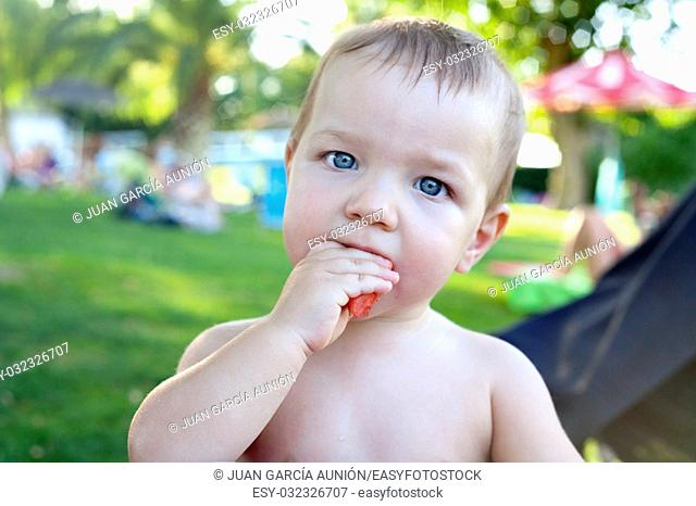 1 year baby boy eating refreshing watermelon after swim. Grass background